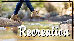 Woman jumping across a stream with the word recreation.