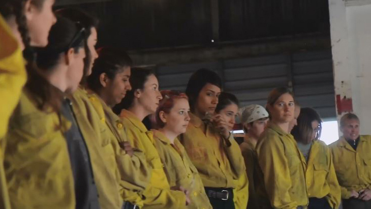 A line of women dressed as Forest Service firefighters stand during a training class.