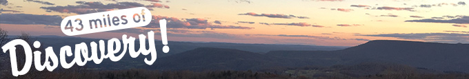 A vista of a sunset over the West Virginia mountains. Text reads 43 miles of Discovery!