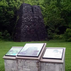 Interpretive signs on stone pillars identifying monument in background