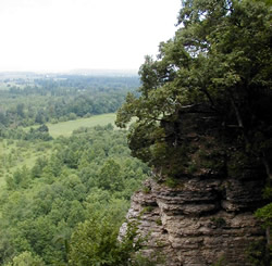 Scenic view from trail looking out at meadow and trees from a rock pinnacle