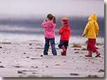 Three youngsters looking for shorebirds at low tide.