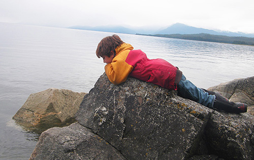 Young boy laying on a rock looking at the ocean below.