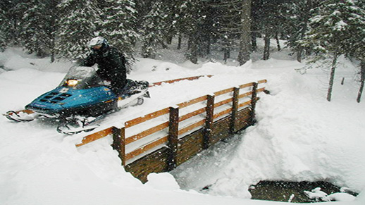 A snowmobiler crosses a bridge in heavy snow.