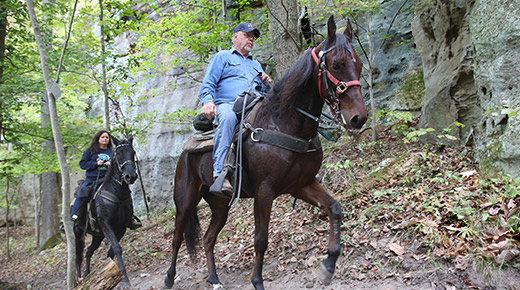 A man and a woman, each on horseback ride along the base of a steep cliff.