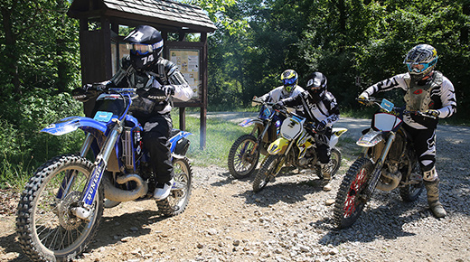 Two men sit on dirt bikes, geared up in protective equipment, smiling