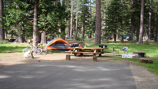 A campsite with a tent, bicycles, and chairs near a fire pit.