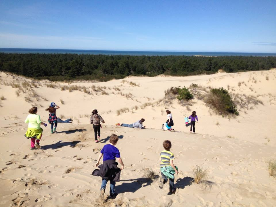 A group of kids run through the sand dunes