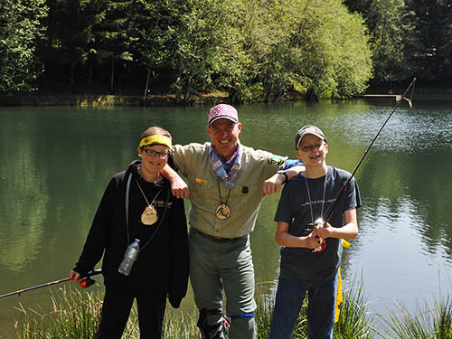 Two kids holding fishing poles pose with forest service ranger