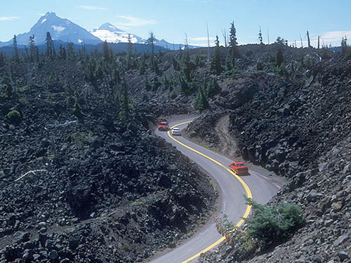 Cars drive over the McKenzie Pass through lava fields