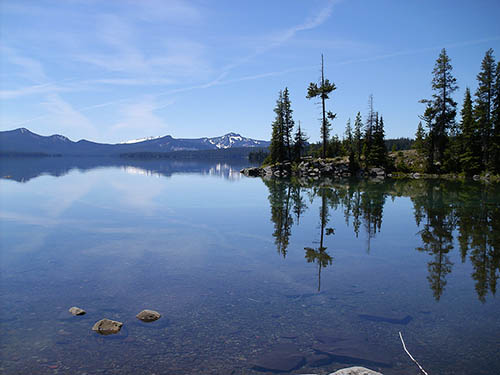 Waldo Lake on a clear day with the lake reflecting the surrounding landscape