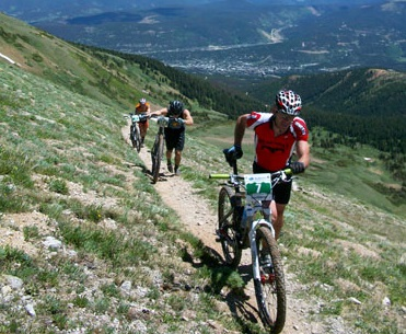 Mountain bikers climb up a rocky trail