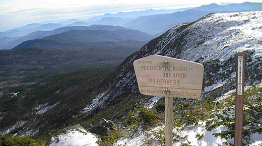 A wooden sign welcoming visitors to the presidential range wilderness overlooks a mountain vista.
