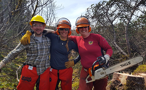 Yakutat NCCC Members pose with a chainsaw Web