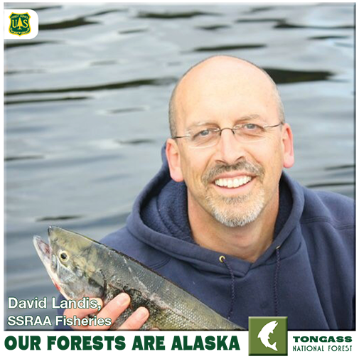 David Lanis holding a fish, water in the background