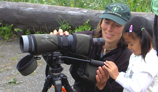 Seasonal Wilderness Ranger Kristen Stelk helping a young visitor to learn to use a spotting scope.