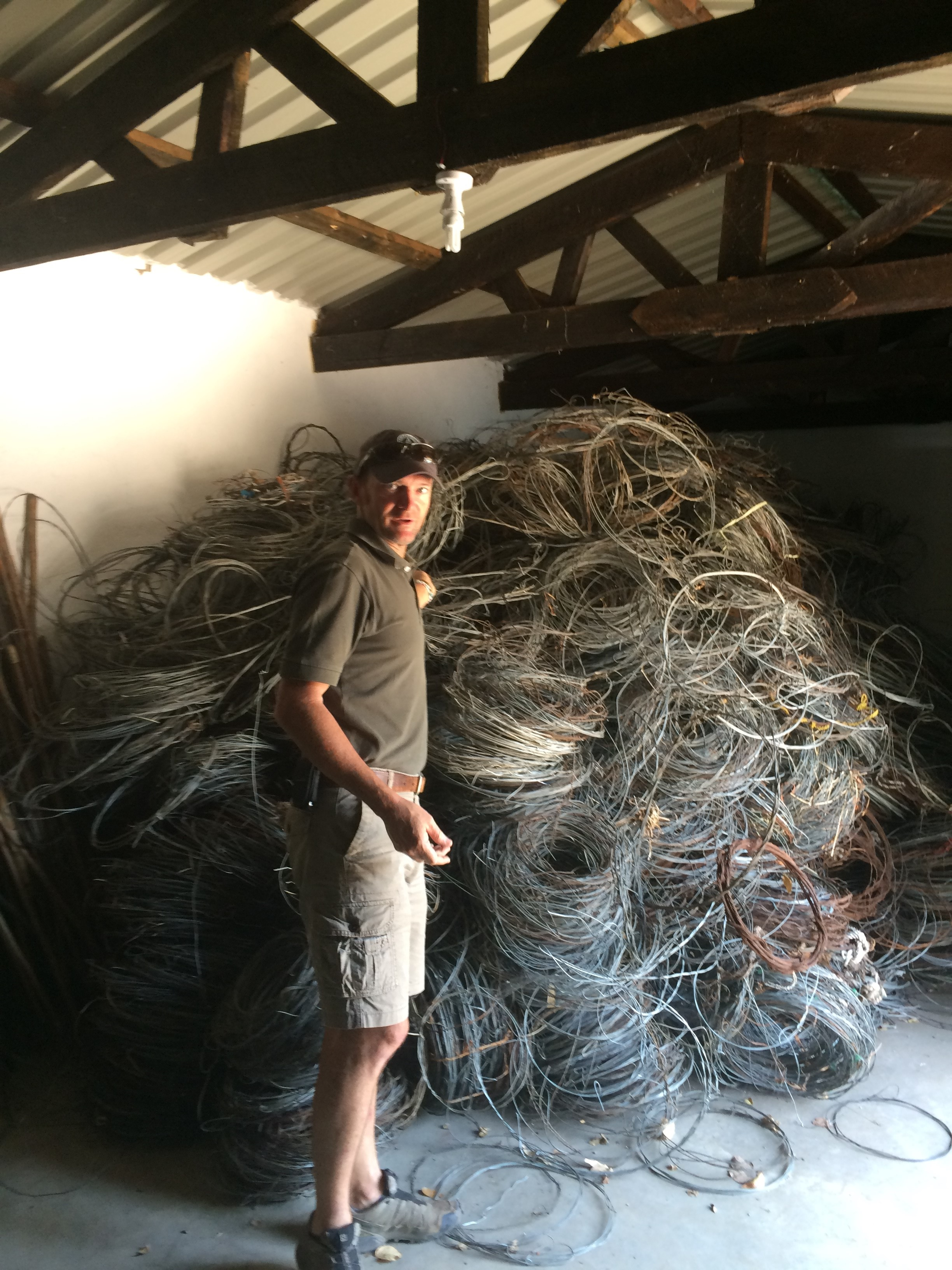 Man standing infront of a large pile of metal snakes