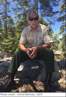 A man in Forest Service uniform sits on a log in a forest.