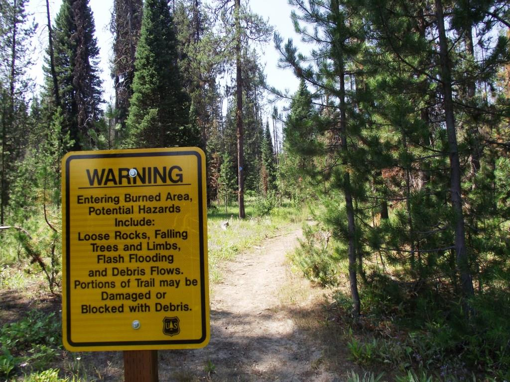 Photo of a sign in wooded area warning of dangers