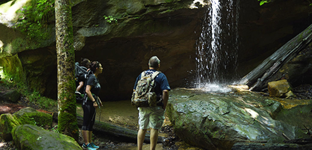 A family hiking,mother with her daughter in a backpack, stare up in wonder at a canyon waterfall.