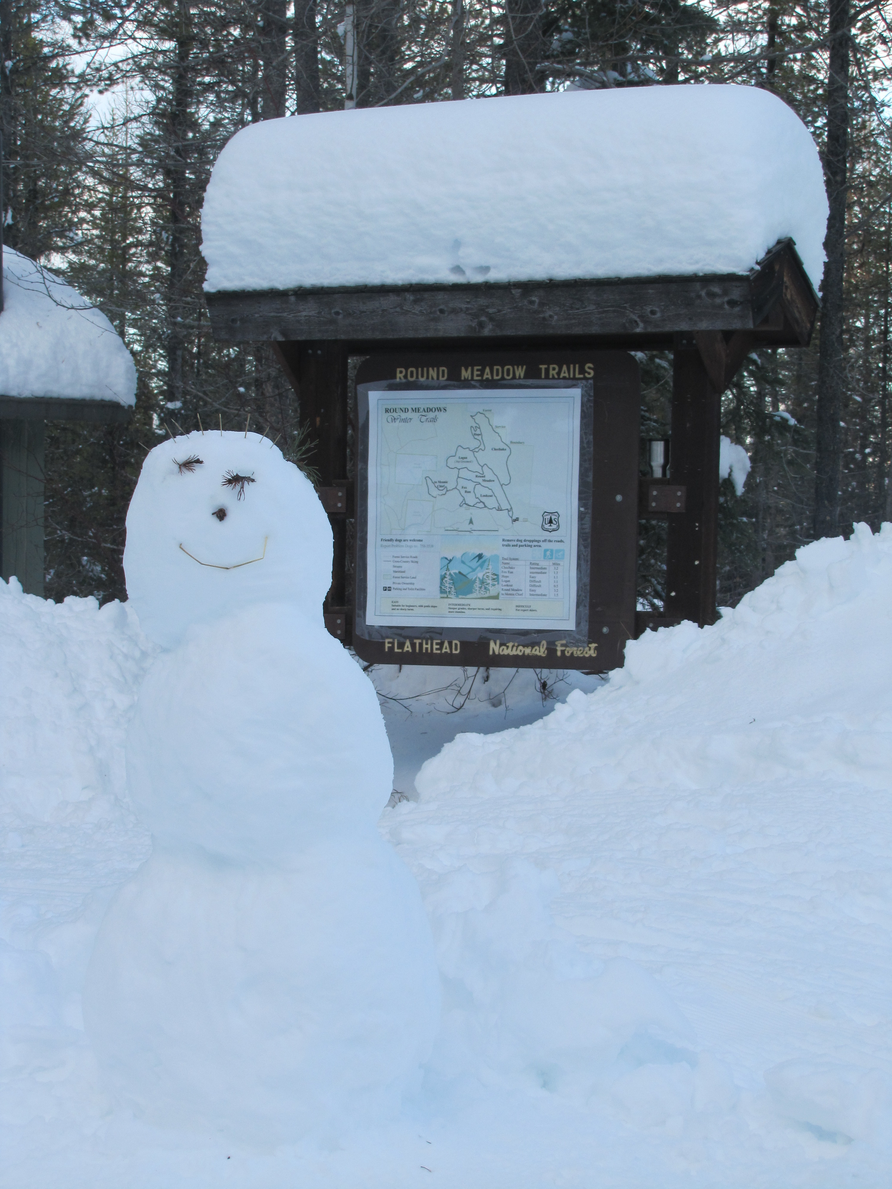 A photograph of a snowman and the trailhead sign for Round Meadows Nordic Area Trailhead