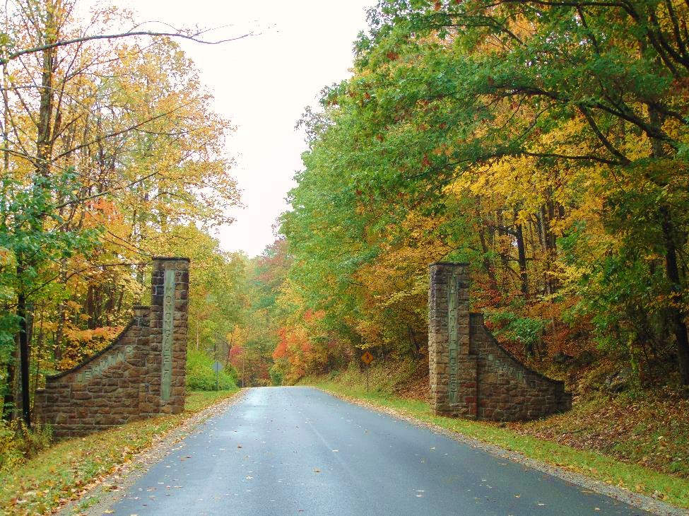 The stone gates of the Stuart Rec Area sit against a yellow backdrop of fall.