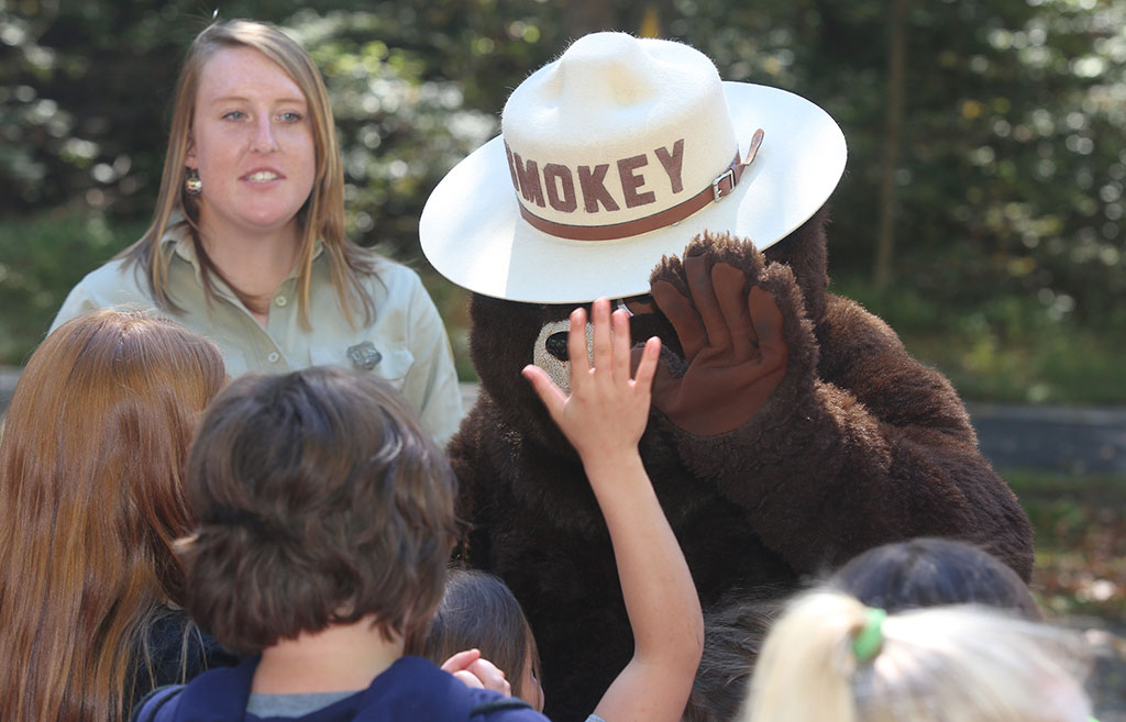 Smokey the bear meets a group of kids with smiles and high fives.