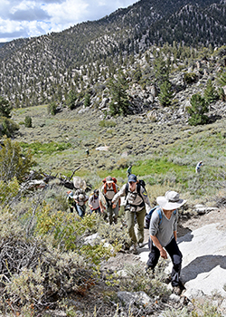 A group of researchers hike into steep mountainous terrain.