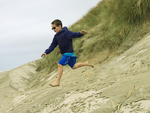 An 8 year old boy runs down a sand dune