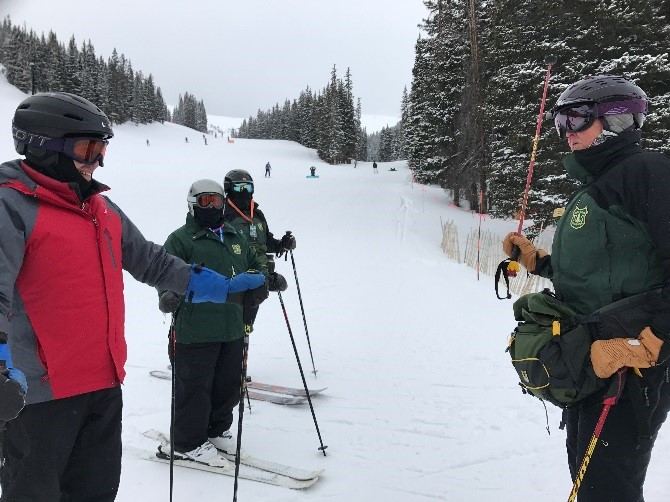 A U.S. Forest Service ski ranger speaks to a guest on the slopes
