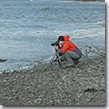Irene Owsley photographing on a beach in Adak.