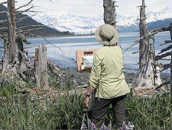 A person painting a picture outdoors