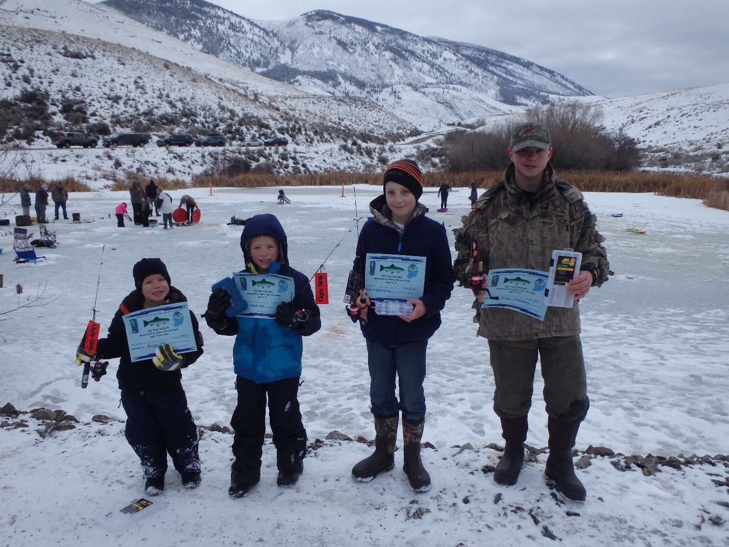 Photo of four kids who attended the Ice Fishing Derby are holding fishing poles and certificates.