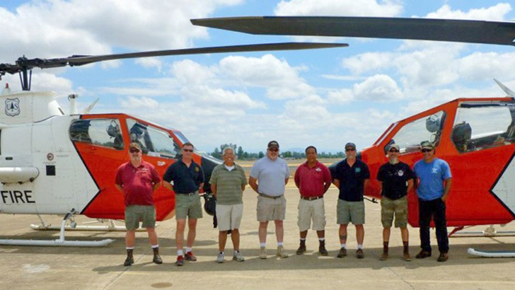 A group of men stand between two Cobra helicopters.