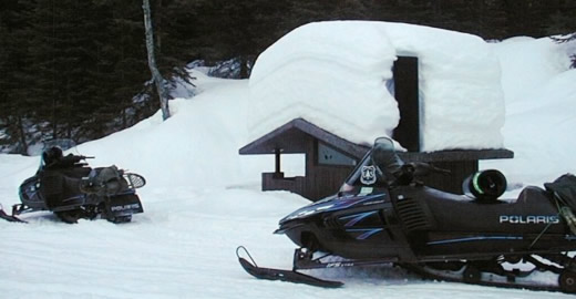 Snowmobiles parked near a snow-covered outhouse