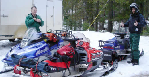 Snowmobiles parked in a snowmobile parking lot, with a snowmobile trailer in the background