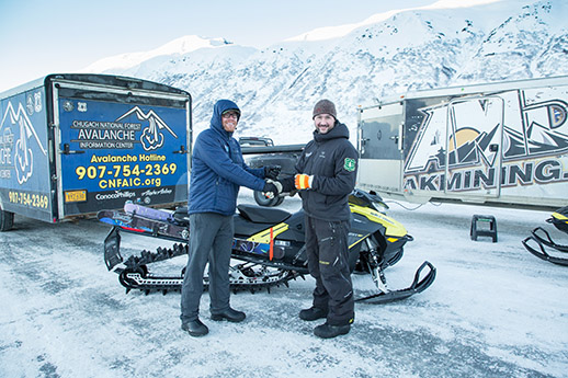 Two guys shaking hands in front of a snowmachine.