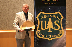 Photo of a ranger holding a wooden bowl award.