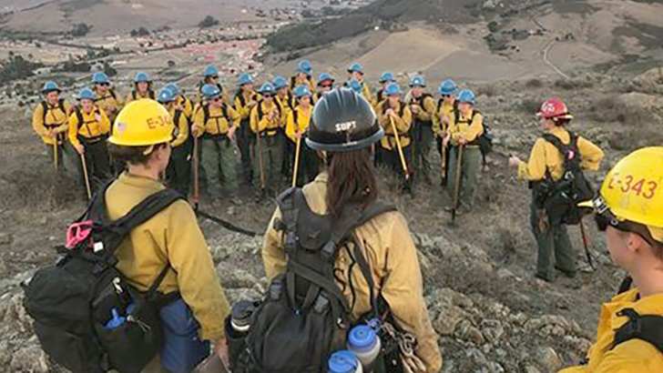 Women firefighters gather in a formation to hear next instruction while standing in an open mountainous area.