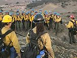 Women firefighters gather in a formation to hear next instruction while standing in an open mountain