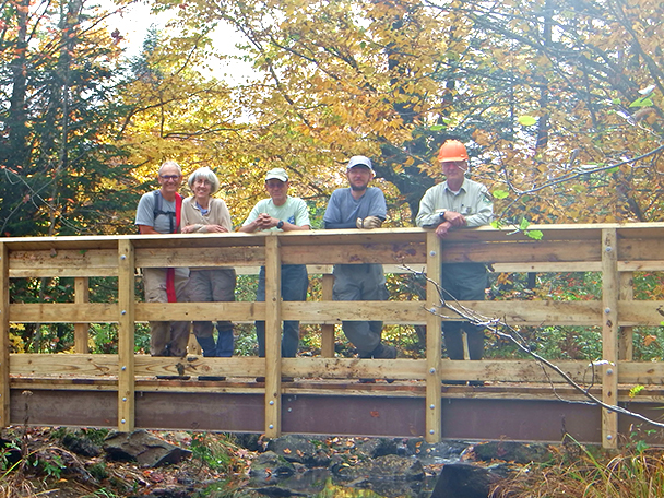 Four volunteers stand across a i-beam bridge in the warm sun of fall.