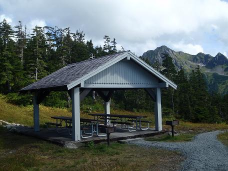 opened picnic shelter with two picnic benches, trees and mountains in the background
