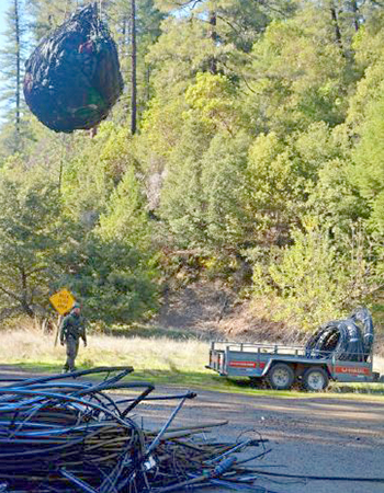 A large net filled with trash bags and irrigation pipes hangs from a rope and carried by a helicopter.