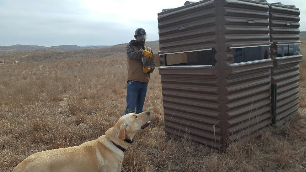 A man and a yellow lab standing in front of a grouse blind.