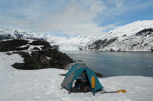 A colorful tent pitched on a snowfield in front of the water.
