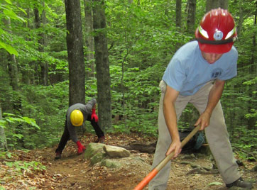 Two young men work on trails, one with a shovel the other with a pick ax.