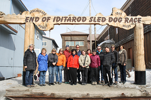 A group of iTREC! students and instructors in front of the Nome Iditarod sign.