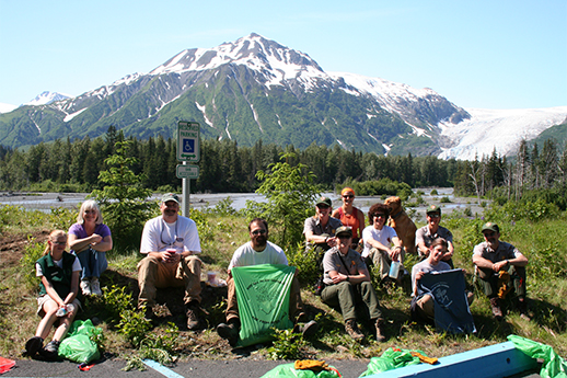 A group sitting with green trash bags after a successful invasive weed pull.