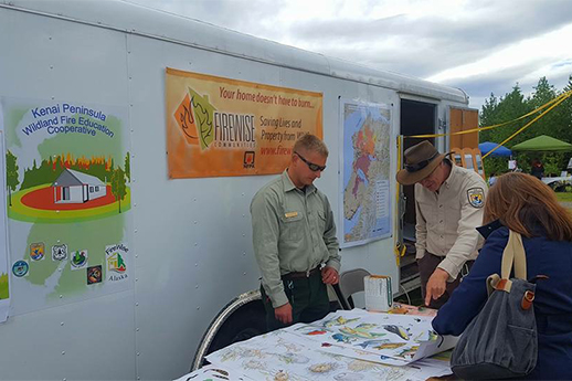 Two public land agency staff are answering public questions and giving out information.