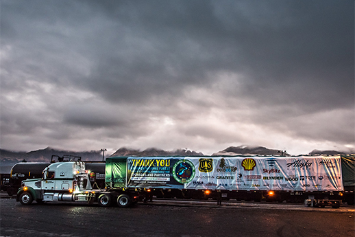 A shot of the Chugach Capitol Christmas Tree truck and trailer with a banner ofall the sponsors.